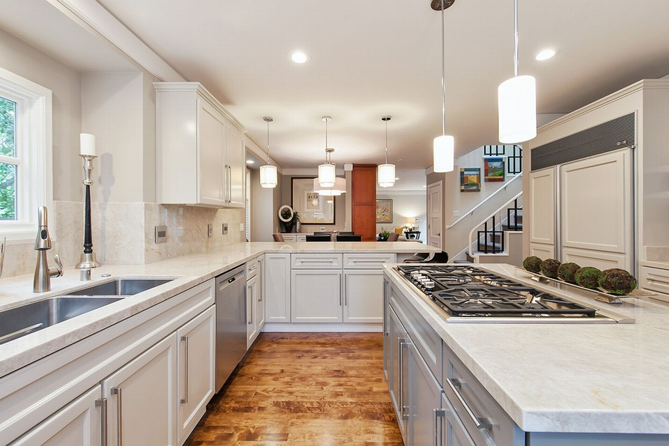 kitchen includes center island, taj mahal slab countertops, custom cabinetry and top-of-the-line appliances